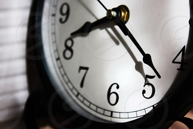 That first glance at the clock face in the morning struggling to focus on the digits the sun casting a shadow of the hands on the clock face. Are you late or on time? photo