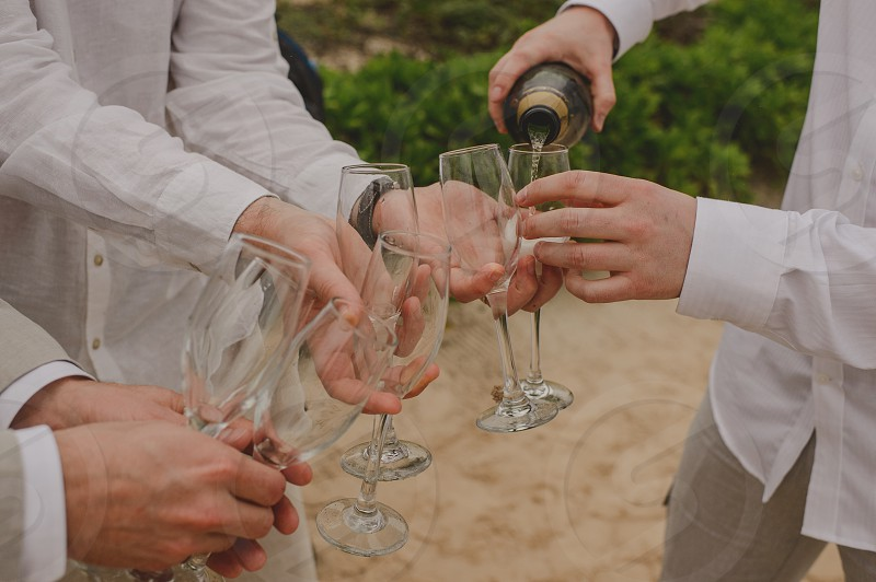 friends in the beach serving champagne photo