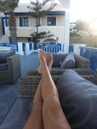 photography of human legs leaning near sofa photo