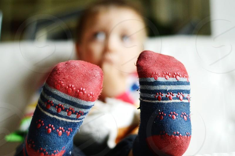 toddler wearing red blue grey socks sitting on white textile photo