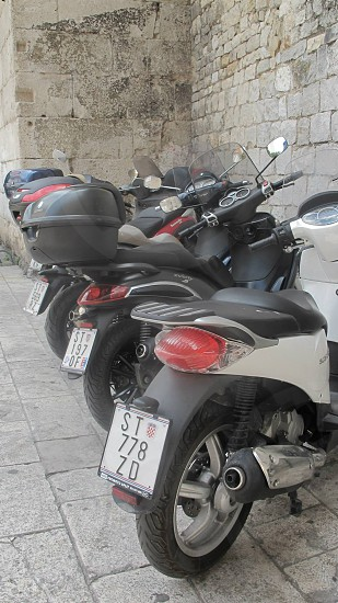 motorcycles scooters parallel ancient wall angled exhilarating tail lights containers mirrors blocks license standing freedom escape fun wind photo