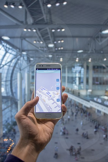 Close up view of male adult hand holding smartphone with 3D map of airport on display and airport terminal in the background photo