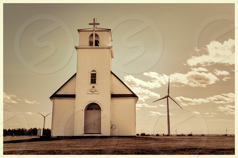 wooden church on grassy field by wind turbines in greyscale photo