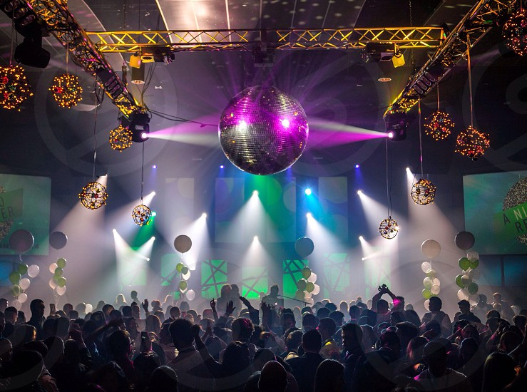 people dancing underneath a large disco ball photo