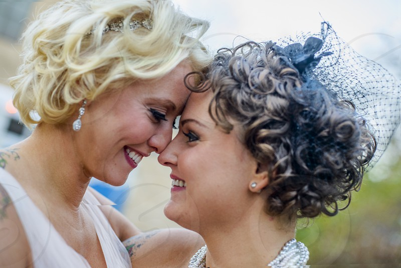 smiling blonde woman face to face with a smiling curly hair brunette both in white photo