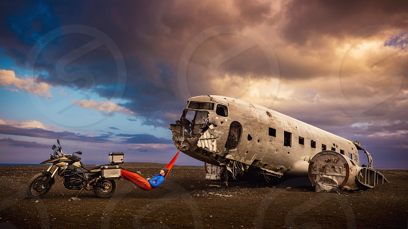 Motorcyclist taking a break in Iceland on a hammock between a motorcycle and airplane on the beach. photo