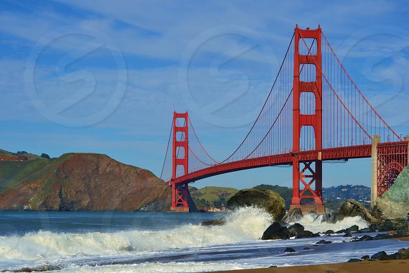 Golden Gate Bridge with blue sky and waves crashing on rocks photo