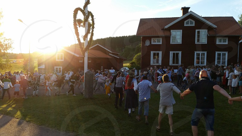 Midsummer celebration with people dancing around the may pole photo