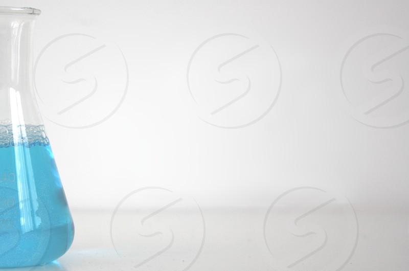 blue liquid in clear glass measuring bottle photo
