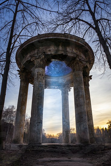 Marvelous old gazebo at sunset time. Fantastic portal in rotunda into space. Front low angle view. photo
