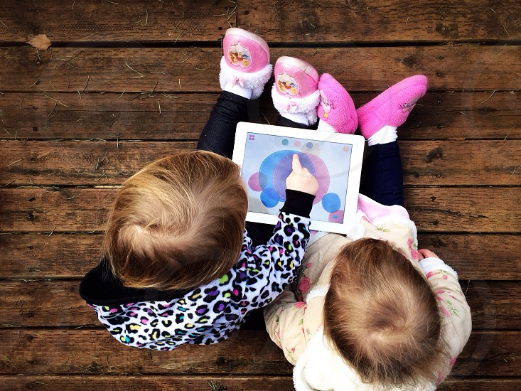 Two young children using an iPad photo