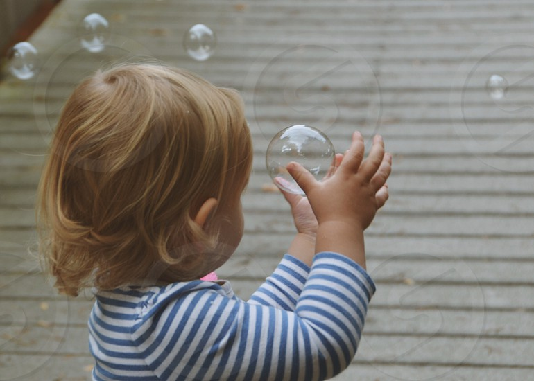 Child trying to catch bubble photo