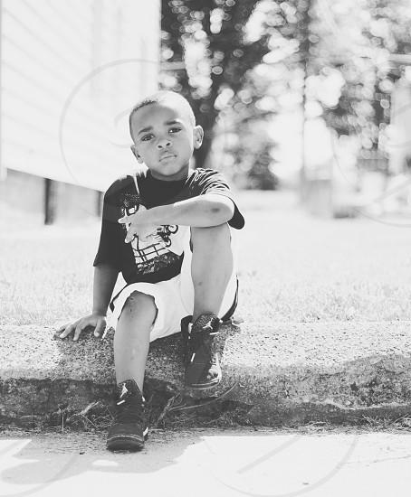 boy wearing black crew-neck t-shirt and white denim shorts photo