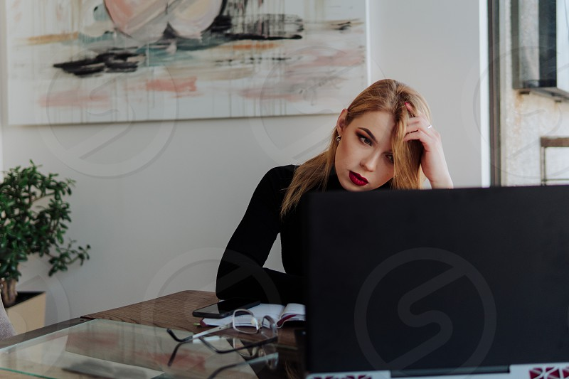 Young beautiful business woman is tired working on the computer supporting her head with a hand photo