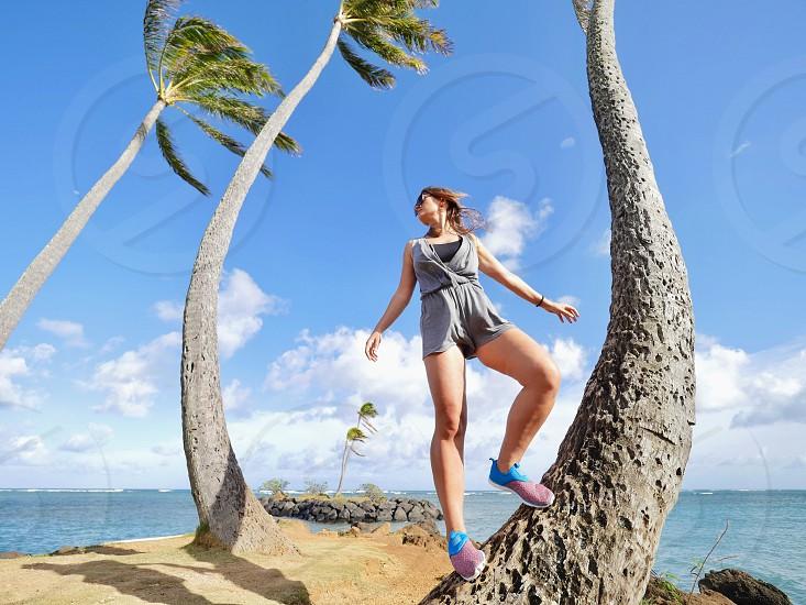 Women standing on a palm tree Adventure among palm trees on the beach Hawaii  photo