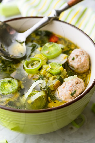 Meatballs an green vegetables soup in a bowl photo