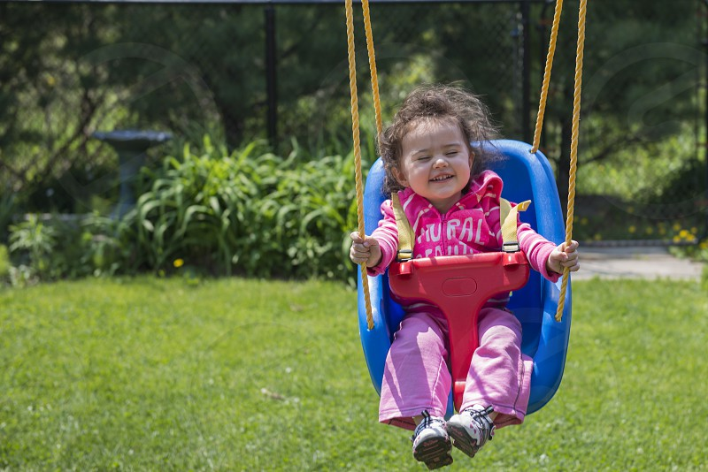 Beautiful little girl playing on swing photo