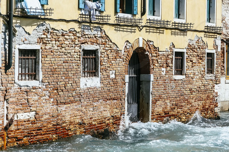 venice building facade door window decaying aged canal high tide flooding patina deteriorating italy house wall photo