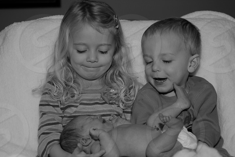 A new baby with brother and sister black and white photo