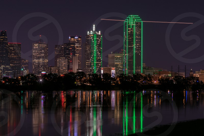 Partial photo of the lights of the Dallas Texas skyline reflecting on the flooded Trinity River with light trail of an airplane passing through the frame in the background. May 31 2015 Photography by Stretch. photo