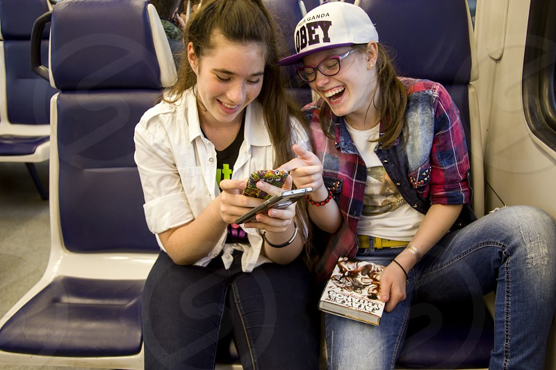 Two teenage girls in the train watching the video in the phone and laughing photo