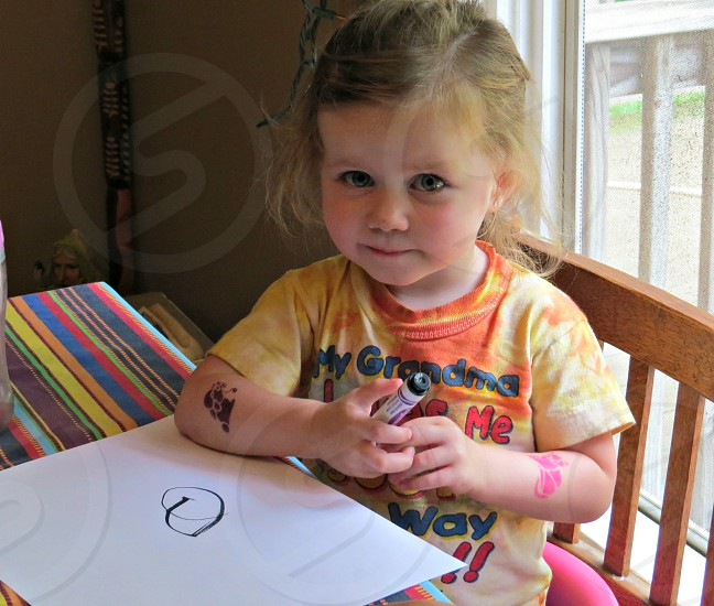 Little girl draws the Global Poverty Project logo. photo