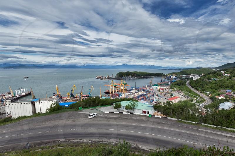 PETROPAVLOVSK-KAMCHATSKY KAMCHATKA RUSSIA - JULY 08 2013: View on city Petropavlovsk-Kamchatsky and commercial seaport. Russia Far East Kamchatka Peninsula Avachinskaya Bay. photo