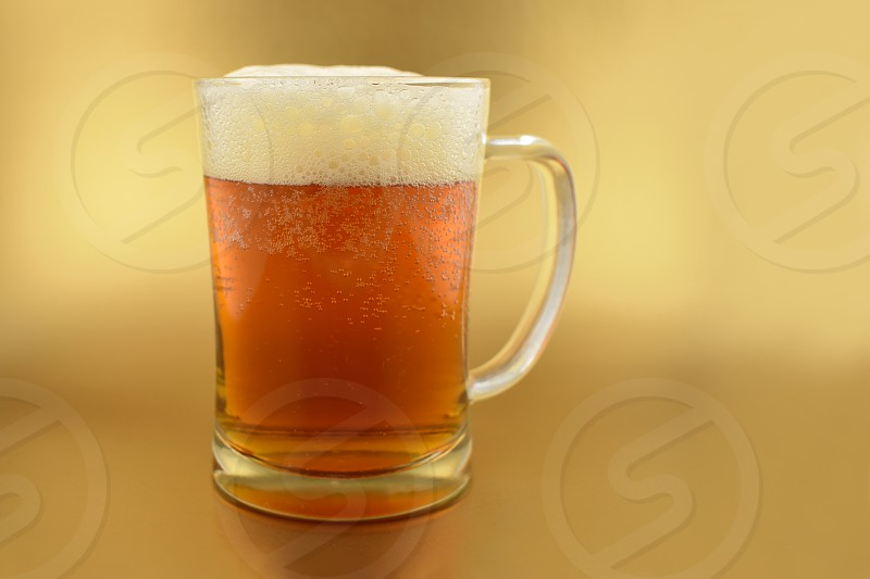 Beer glass with handle. Glass with beer on a golden background. Beer on a golden background with copy space for text. Festive golden background photo
