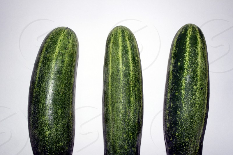 3 green cucumber on white surface photo