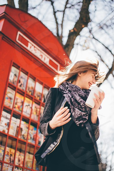smiling blonde woman twirling under the sun holding a white coffee cup by a red phone booth photo