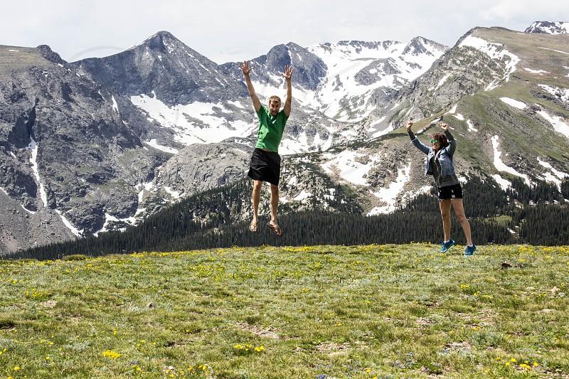 man in green shirt taking selfie while jumping photo
