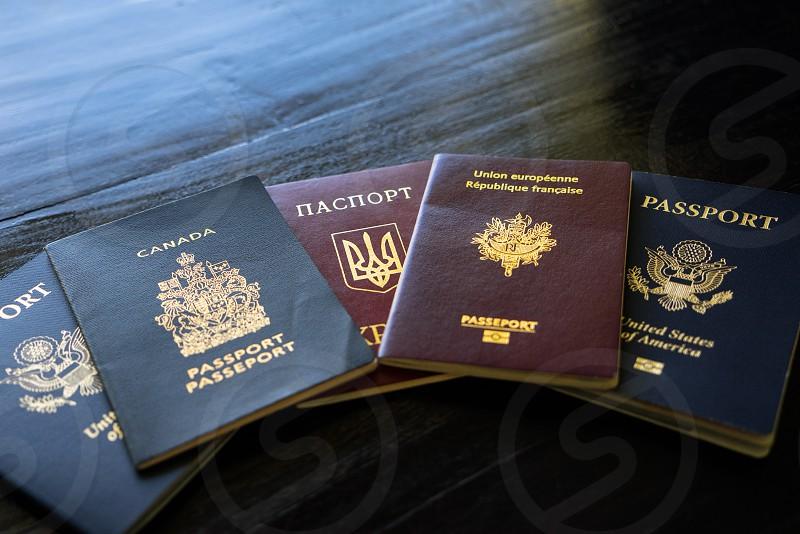 An arrangement of International Passports on a  black wood background photo