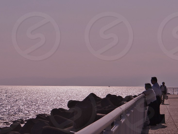 man and woman standing beside sea photo
