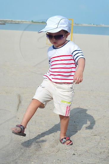 boy walking on beach photo