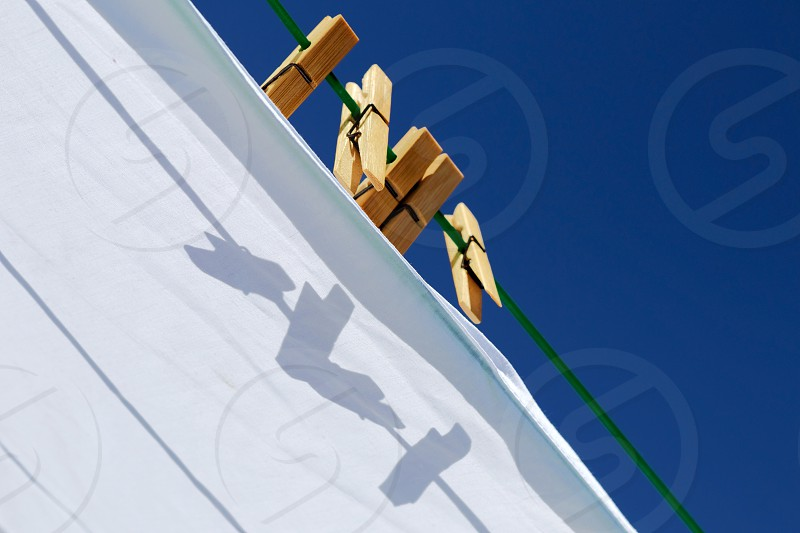 Bamboo clothes pegs on a green clothes line against a blue sky with their shadows on a white sheet drying in the sunshine photo