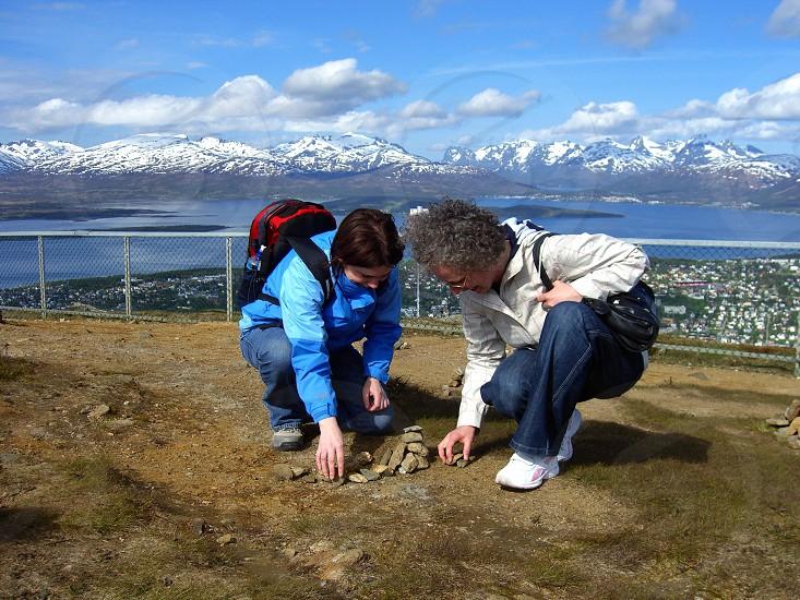 2 women stacking stones photo