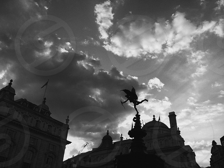 angel statue beside 2 buildings under cloudy skies photo