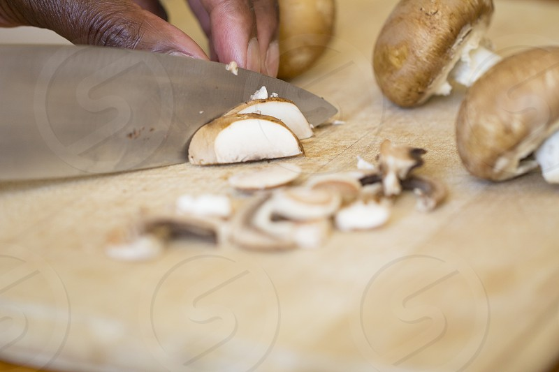 board chopping cooking ingredients wooden black afro american african man knife cook raw food person sliced preparation cut hand mushroom ingredient chef male slice closeup kitchen focus cutting preparing food chop kitchen board choppingboard wood white mushroom uncooked vegetable white vegetarian human hand edible mushroom slicing work cutting board chopped slices prepare brown vegetables; caribbean photo