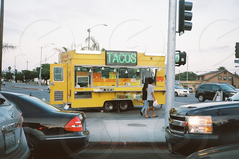tacos yellow food truck parked on gray pavement near city street photo