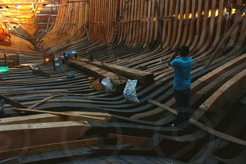 man taking pictures while inside unfinished wooden ark photo