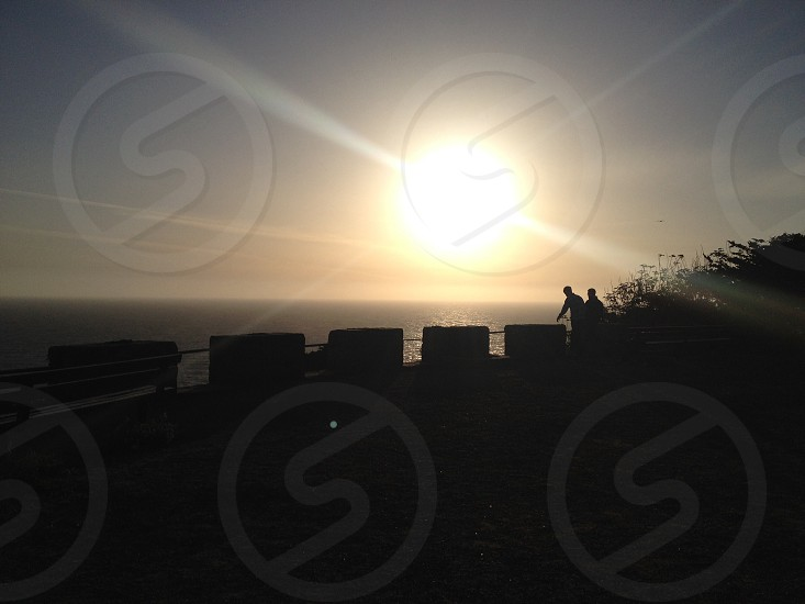 silhouette photography of bridge with two person leaning on wall photo