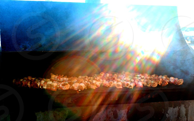 Barbecue skewers on grill in sunlight photo
