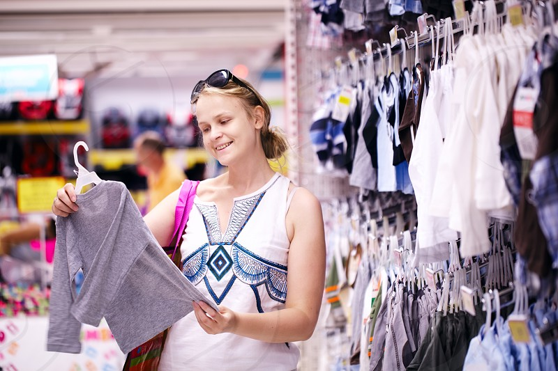 Attractive young mother shopping for childrens clothes in a retail clothing store viewing items on a rack photo