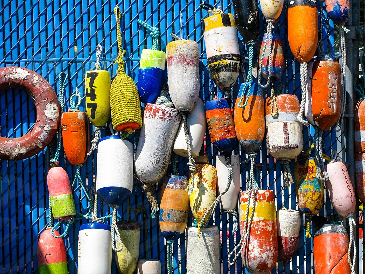A group of brightly colored fishing buoys hangs on display at Charleston Harbor near Coos Bay Oregon USA photo