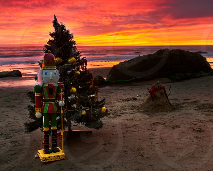 A Christmas scene at the beach at sunset. A large nutcracker a snowman and a Christmas tree sit on the sand. photo