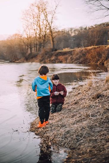 Kids boys brothers playing lake fall photo