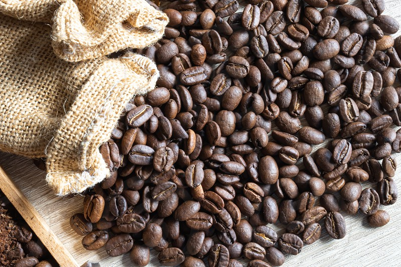 close up Roasted coffee beans in small sack  on wooden table photo
