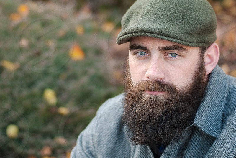Bearded man with cap sitting in outdoors photo