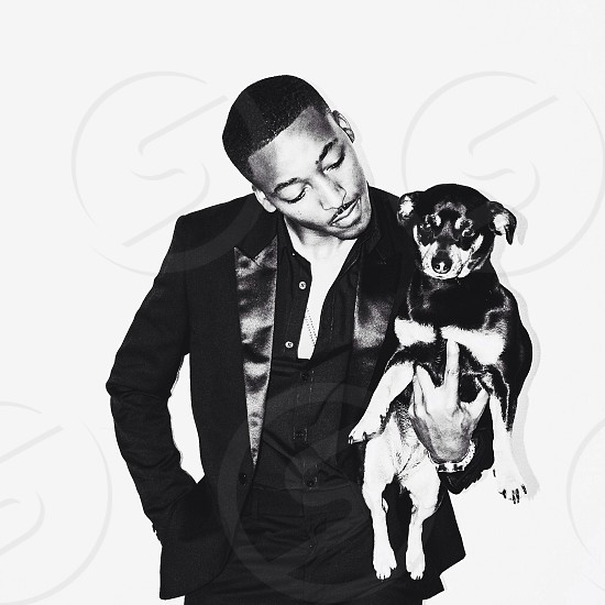 man in black suit holding black and white short haired small dog photo