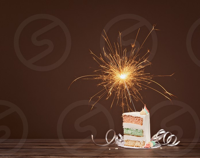 Slice of layered Birthday cake with lit sparkler against a brown background photo